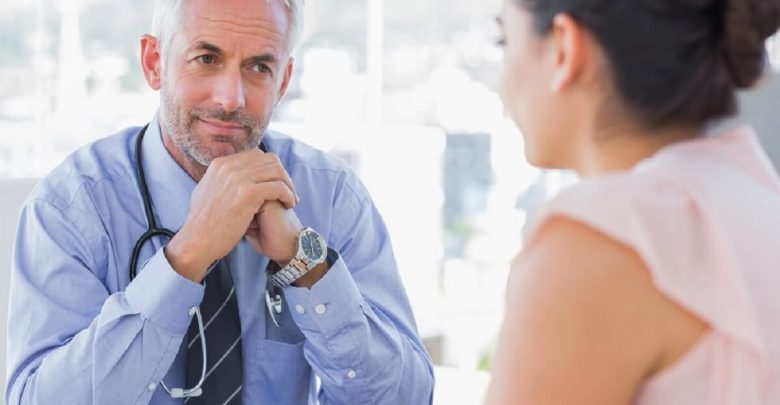 Serious doctor listening to patient explaining her painful in his office