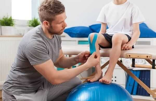 Physical therapist applying young patient medical tape