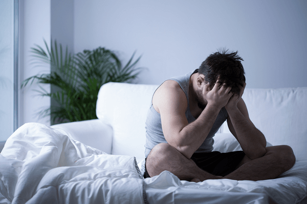 Young man having depression sitting on the bed