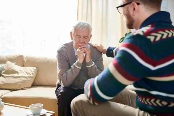 Back view portrait of male psychologist consoling depressed senior man during therapy session