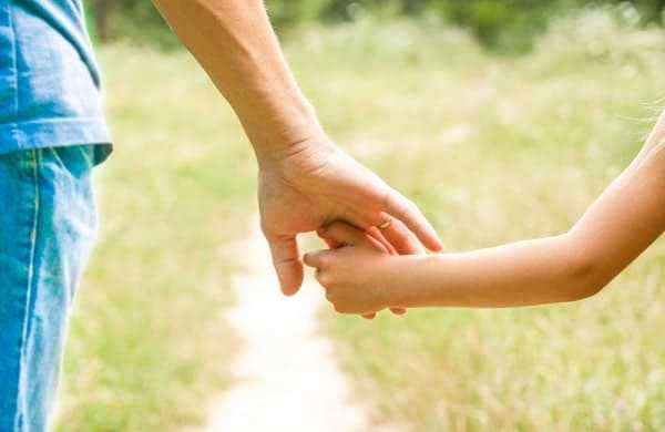 the parent holding the childs hand with a happy background