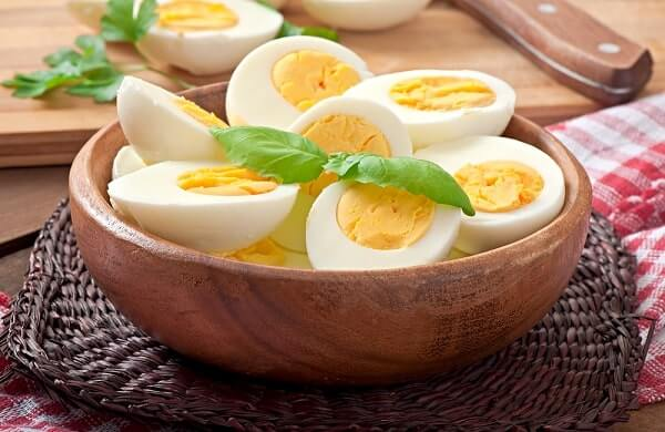 Boiled eggs in a bowl decorated with parsley leaves