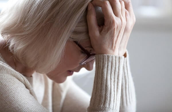 Stressed sad tired middle aged senior woman holding head in hands feeling headache migraine