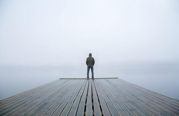 Young man standing alone on edge of footbridge and staring at lake