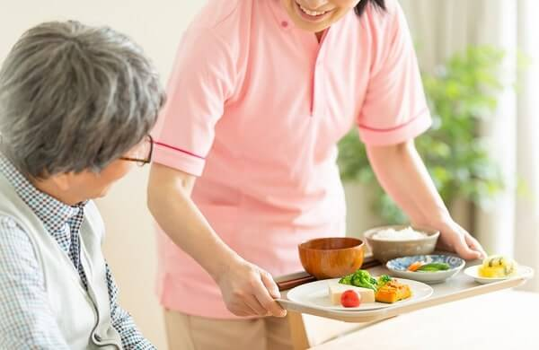 caregiver brings food to patient