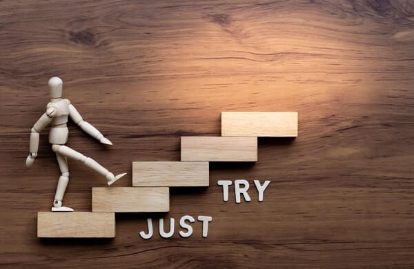 "Ascending stairs and wooden man model going upward with text ""just try' on wooden background"