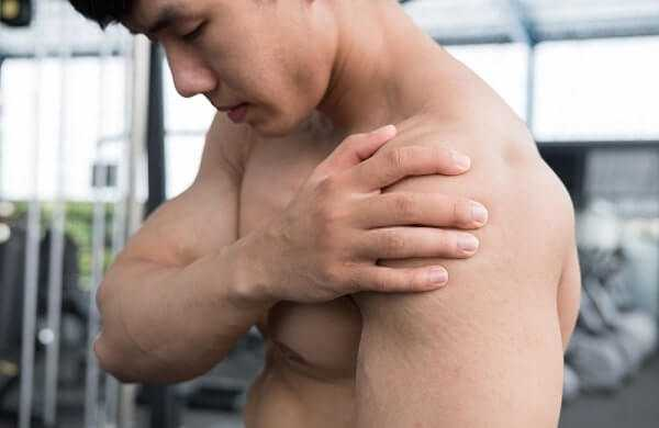 muscular male having pain on shoulder in gym