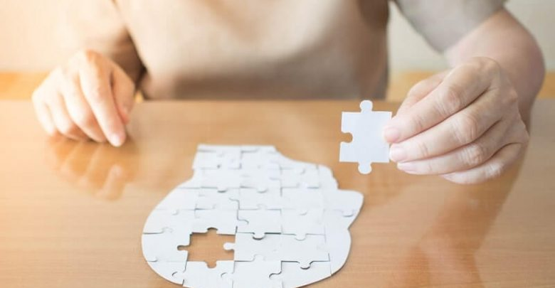 Elderly woman hands holding missing white jigsaw puzzle piece down into the place as a human head brain shape