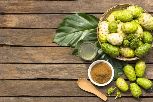 Noni fruit and noni in the basket with noni juice and noni powder on wooden table