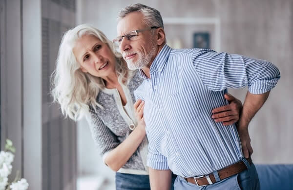 Handsome old man is having back pain and his attractive old woman supports him
