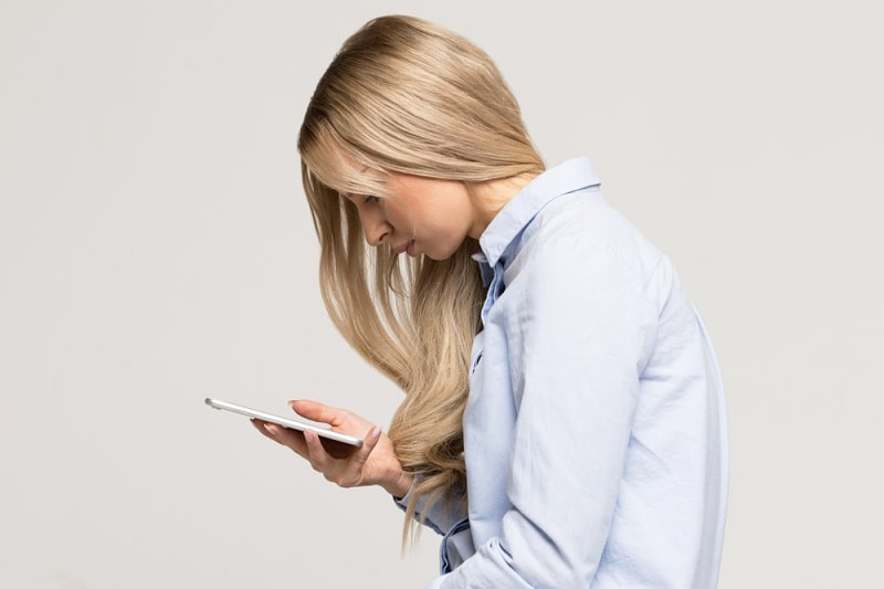 Close up portrait of young Caucasian woman looking and using smart phone with scoliosis