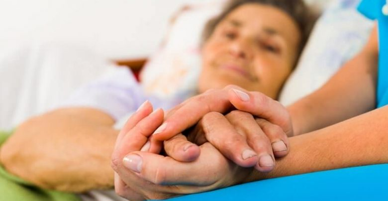 Caring nurse holding alzheimer patient hands in bed