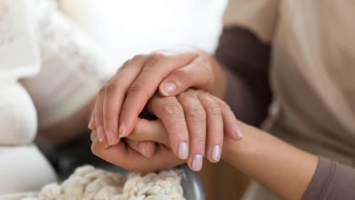 a female caregiver and senior woman holding hands