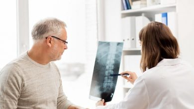 doctor showing x-ray of spine to senior man at hospital