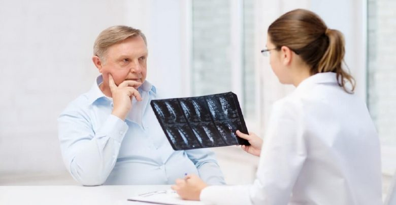 female doctor with old man looking at x-ray
