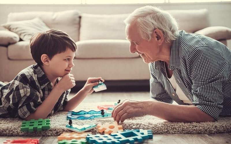 Grandpa and grandson are playing with toys