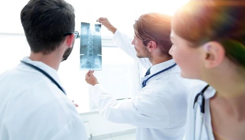 happy surgeons holding x-ray report
